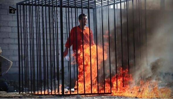 Flames begin to immolate Moaz al-Kasasbeh.