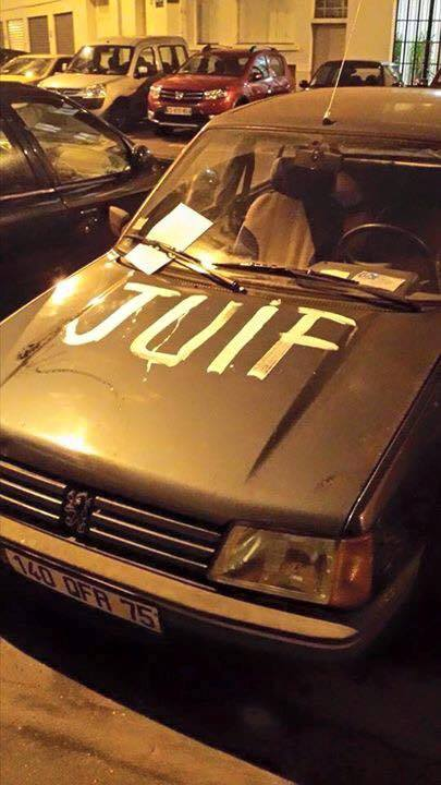 A car with the word, 'Juif' (Jew) spray-painted on the hood.