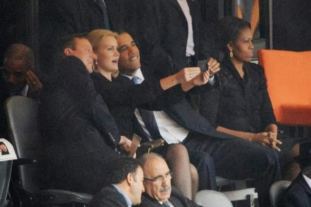 British Prime Minister David Cameron, Danish Prime Minister Helle-Thorning Schmidt and U.S. President Barack Obama take selfie at Nelson Mandela's funeral. Michelle Obama sits apart, unamused.