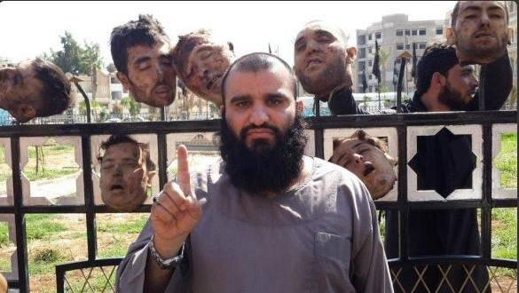 Fat ISIS terrorist raising 1 finger in front of iron fence with 5 human heads impaled on fence spikes. A man in the background adds 2 more heads to the grisly scene.