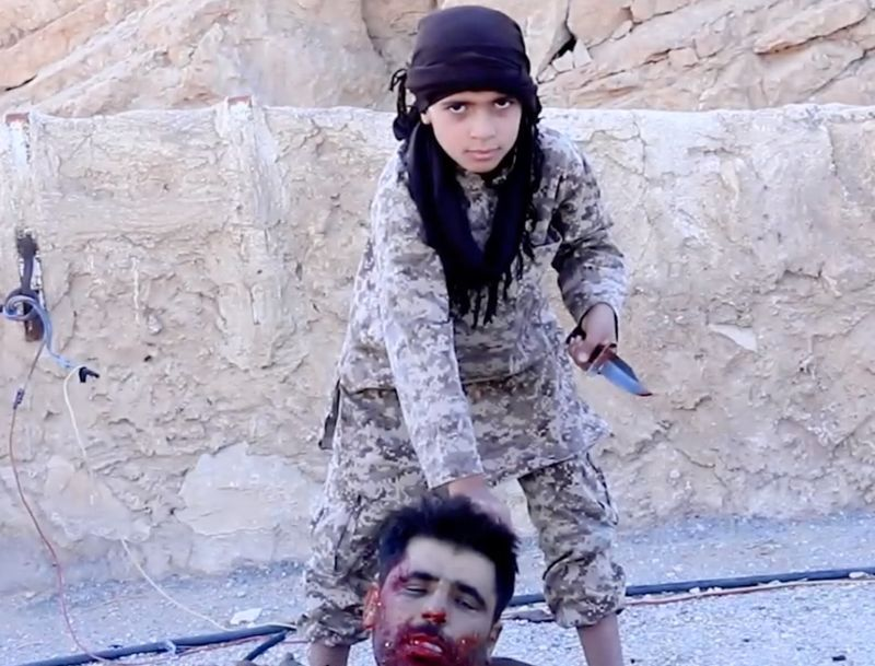10 year old boy with dagger holds severed human head.