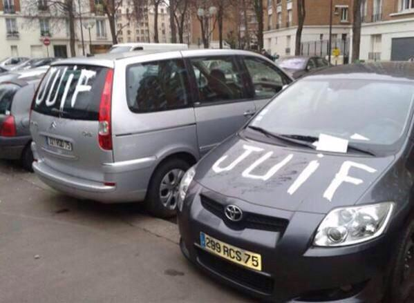 Two cars spray-painted with the word, 'Juif' (Jew).